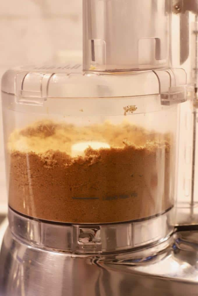 Using a food processor to make crumbs out of gingersnap cookies for Pumpkin Cheesecake with Gingersnap Crust