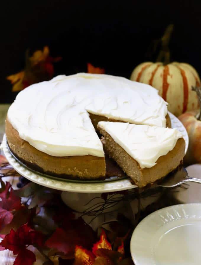 Pumpkin cheesecake on a cake stand with a slice cut out.