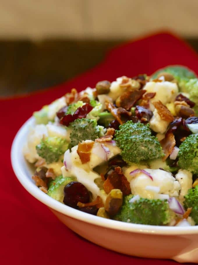 Broccoli Cauliflower Salad with Cranberries in a white serving bowl.