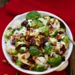 Broccoli Cauliflower Salad with Cranberries in a white serving dish on a red napkin