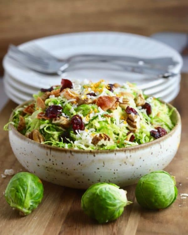 Brussel Sprouts Salad with Citrus Vinaigrette topped with bacon and parmesan cheese.