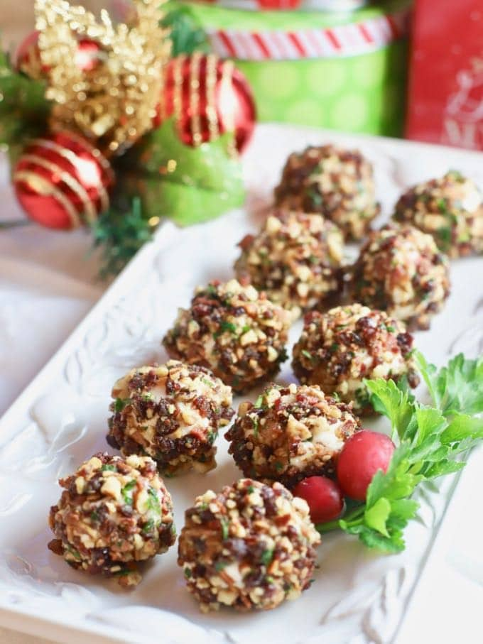 A dozen Cranberry Pecan Mini-Goat Cheese Balls garnished with parsley and cranberries.