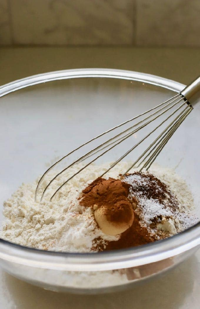 Flour and other dry ingredients in a glass bowl for gingerbread cake.