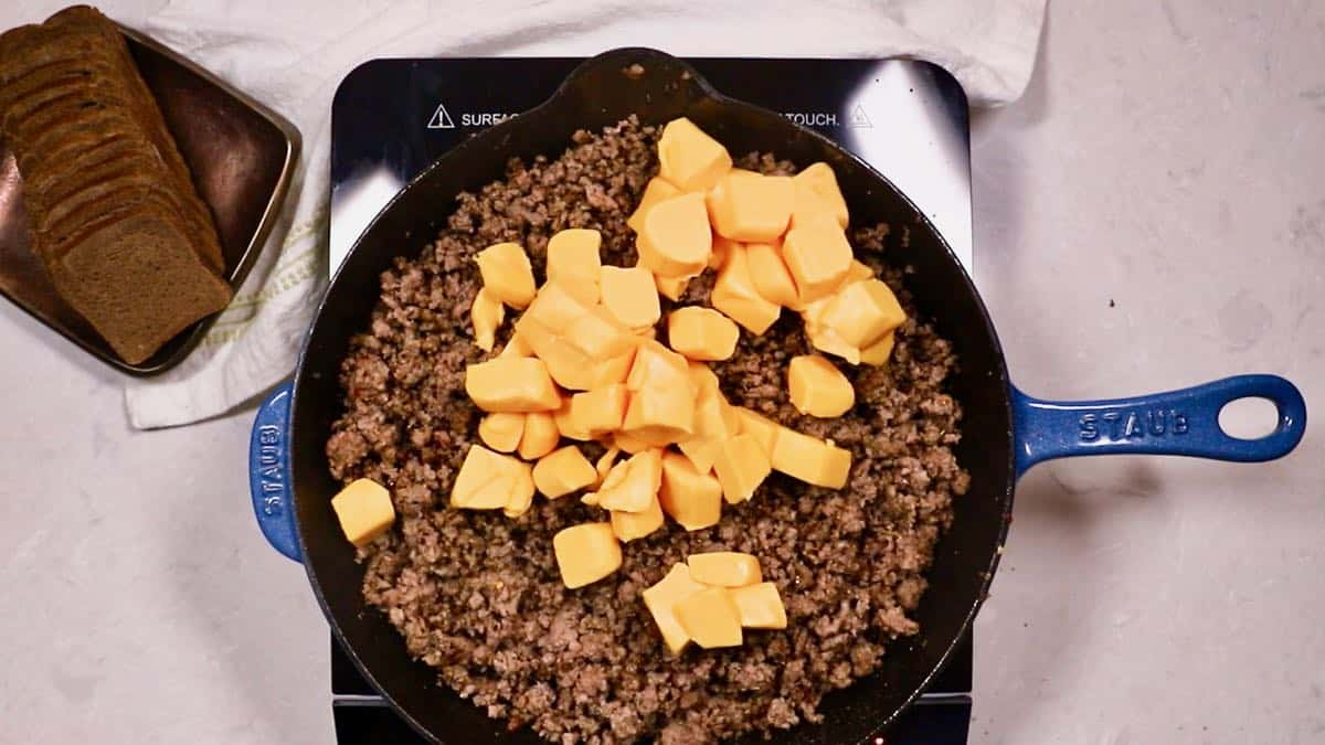 Cubes of processed cheese added to ground beef.