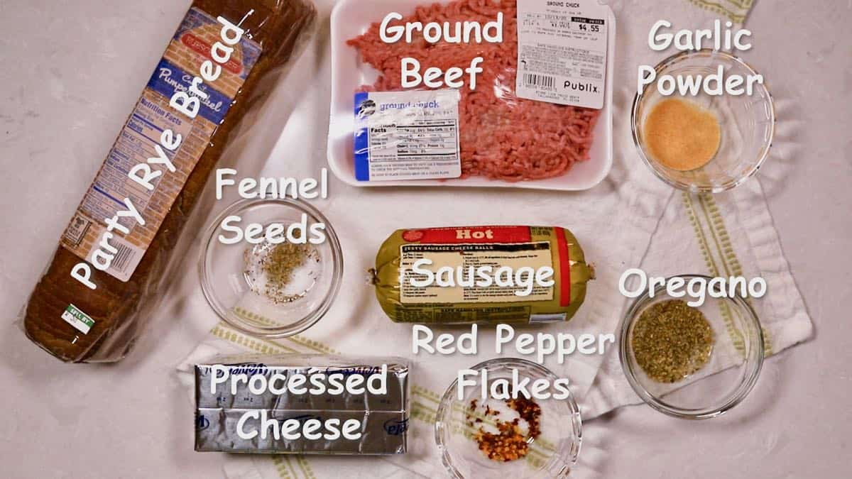 Ground beef, sausage and party rye bread on a counter.