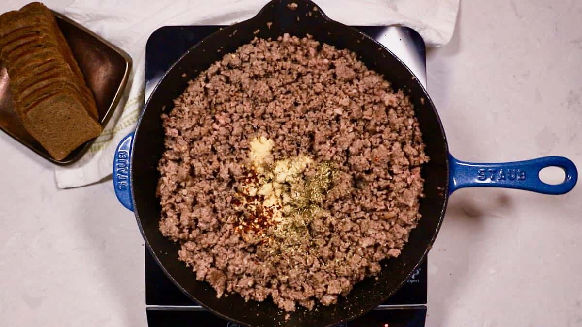 Hamburger meat cooking in a skillet with garlic powder and other spices.