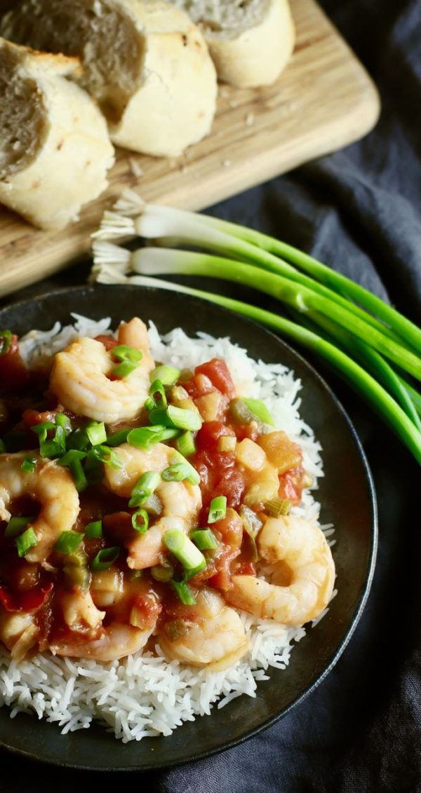 Shrimp Creole in a black cast iron pan with scallions for a garnish.