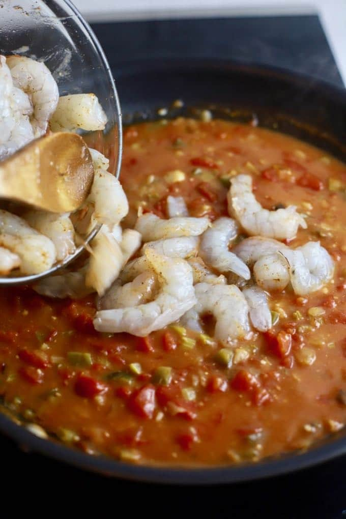 Adding shrimp to a skillet with a spicy tomato sauce to make shrimp creole.
