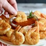 Dipping Easy Crispy Pan-Fried Shrimp in cocktail sauce.