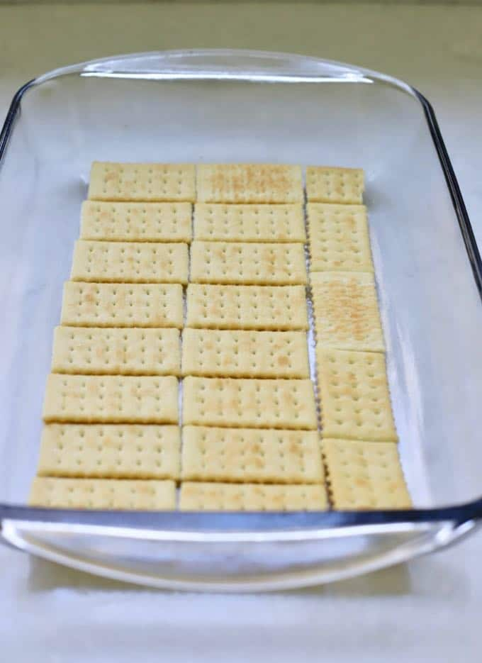 A layer of crackers in a baking dish to make homemade copycat kit kat bars.