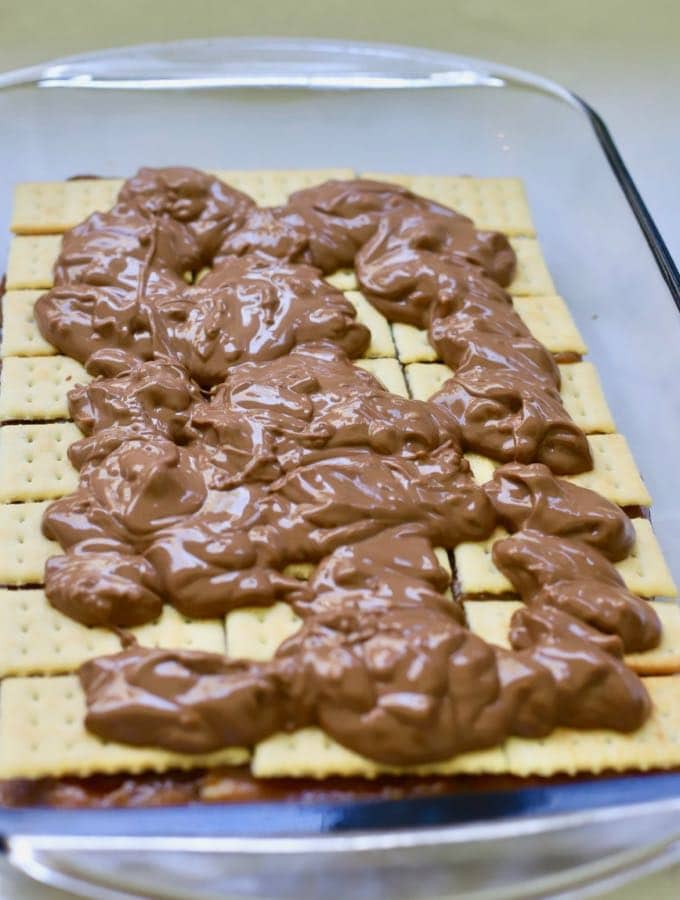 Melted chocolate topping is spread over crackers to make homemade copycat kit kat bars.