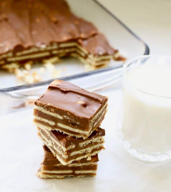 A stack of three homemade kit kat bars with a glass of milk.