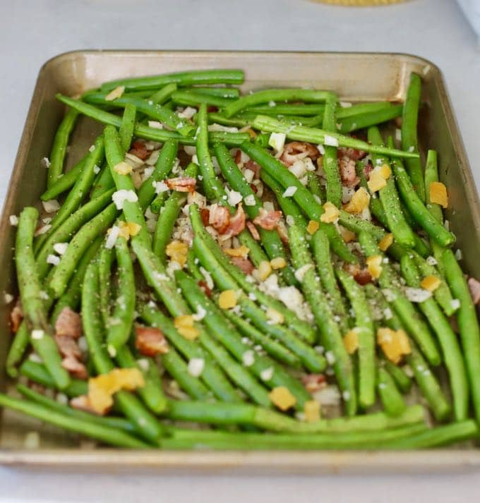 A baking sheet with green beans, onion, preserved lemon peel and bacon ready to roast in the oven.