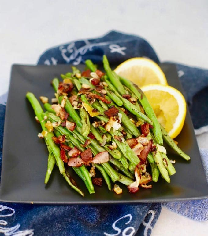 A plate of Roasted Green Beans with Bacon and Lemon.