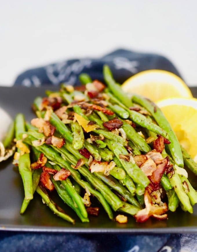 A black plate full of Oven Roasted Fresh Green Beans with Bacon and Preserved Lemon.