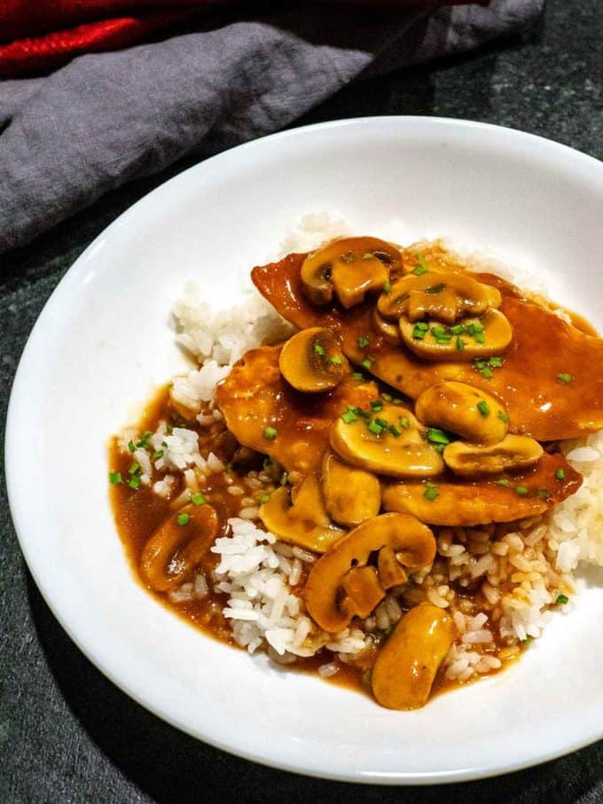 Creamy Chicken Scallopini with Mushrooms in a white serving dish. Part of a roundup of 23 Easy Dinner Party Recipes.