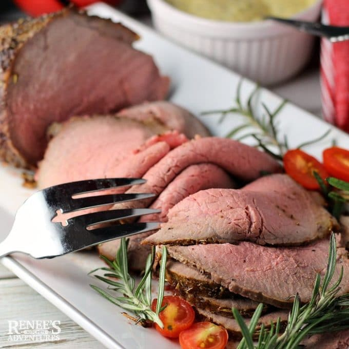 Eye of Round Roast on a white serving platter garnished with rosemary.