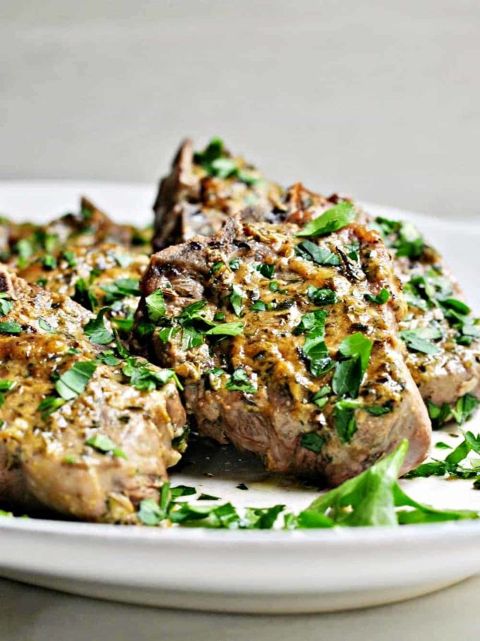 Roasted Lamb Chops garnished with parsley and on a serving platter.