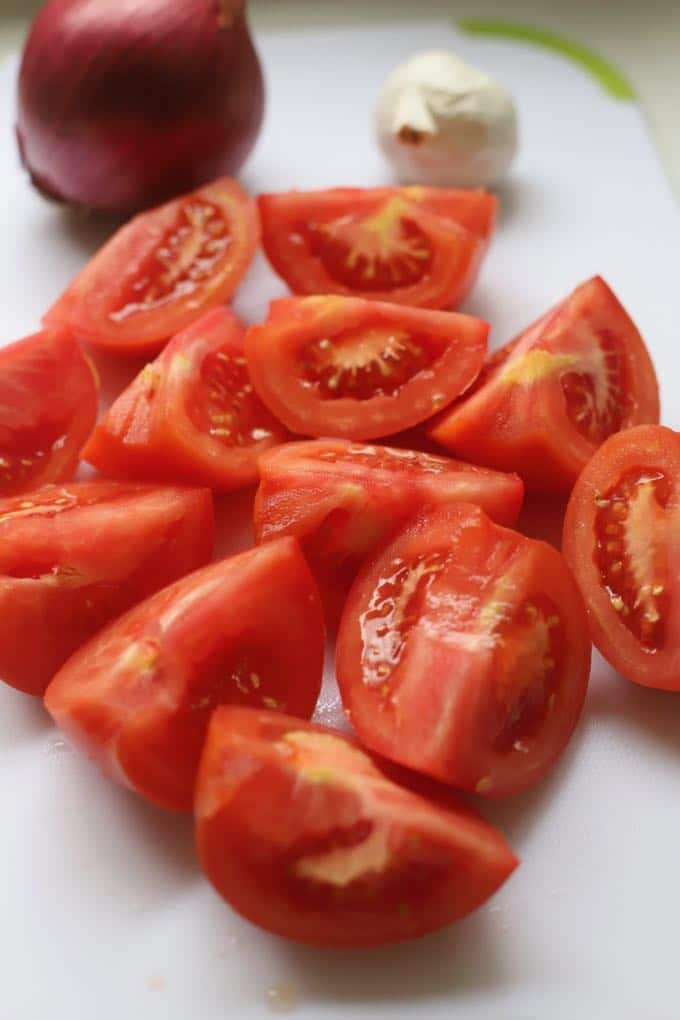 Cored and cut up fresh tomatoes to make tomato soup.