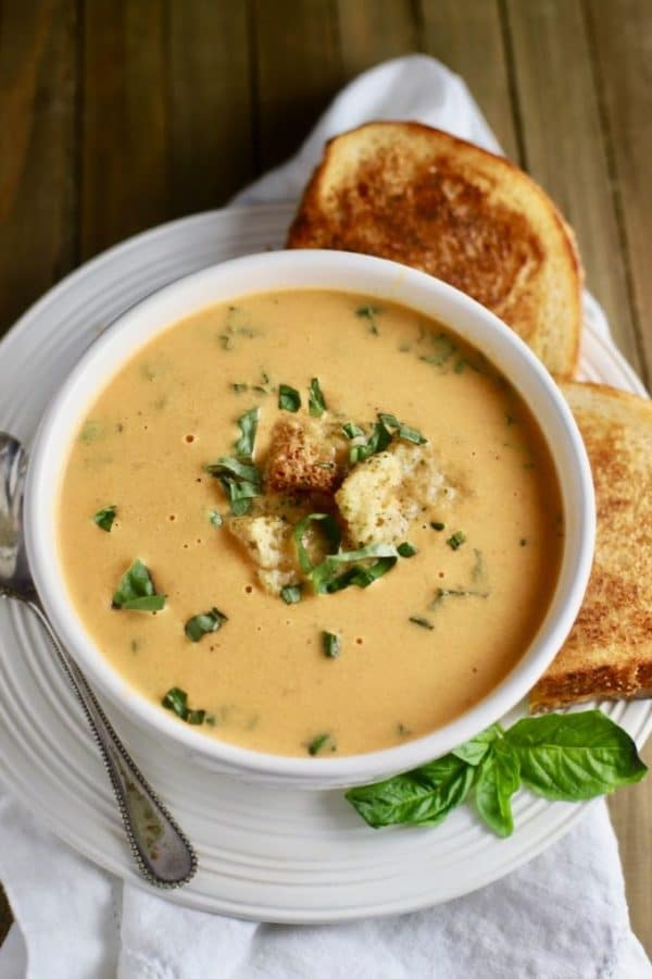 A bowl of Creamy Roasted Tomato Soup with grilled cheese sandwiches.