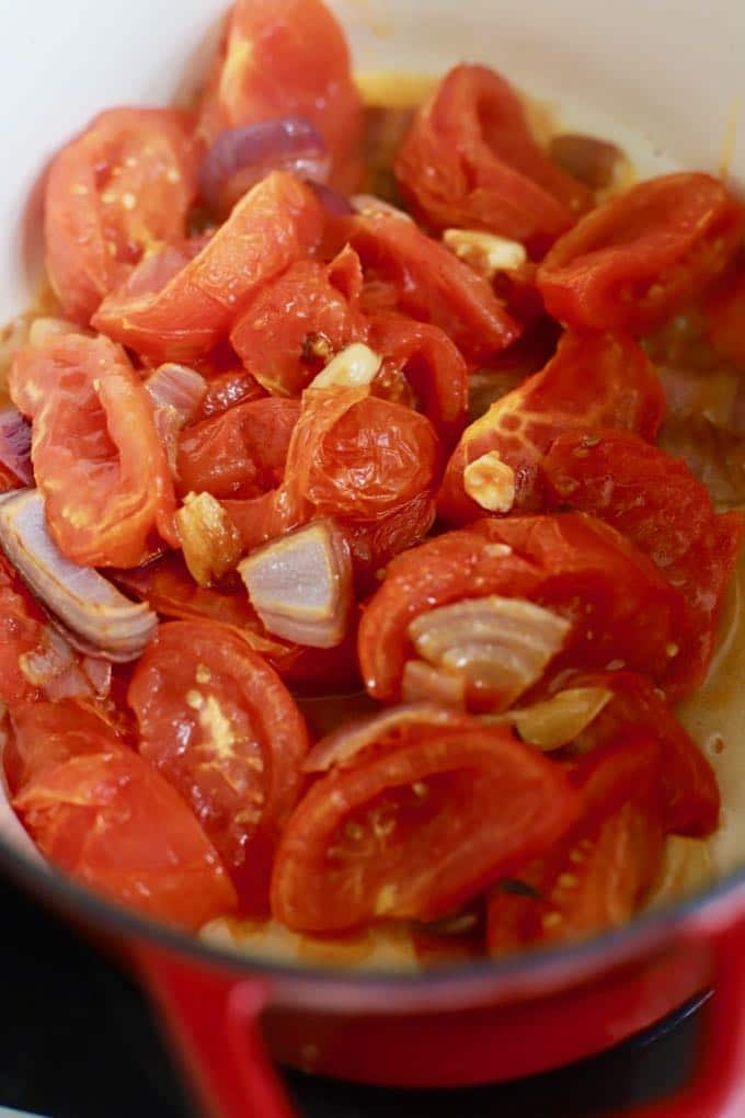 Roasted tomatoes, onions and garlic in a pan to make tomato soup.