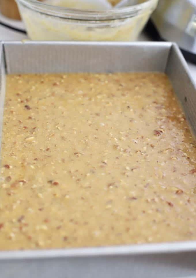 Cake batter in a rectangle metal baking pan.