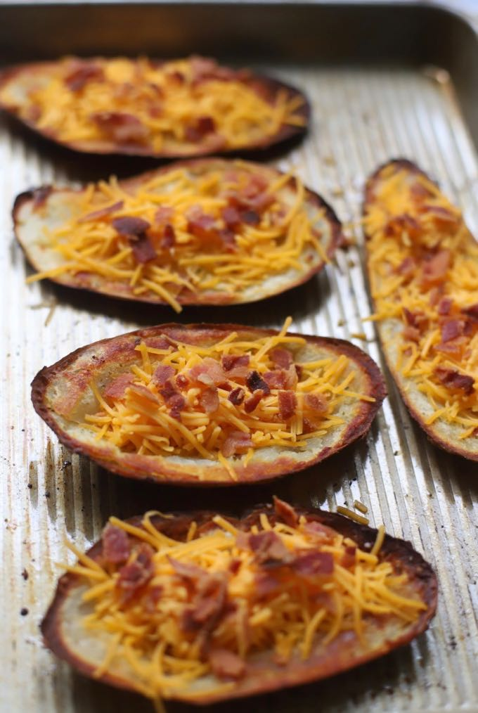 Shredded cheese and bacon top baked potato skins on a baking sheet.