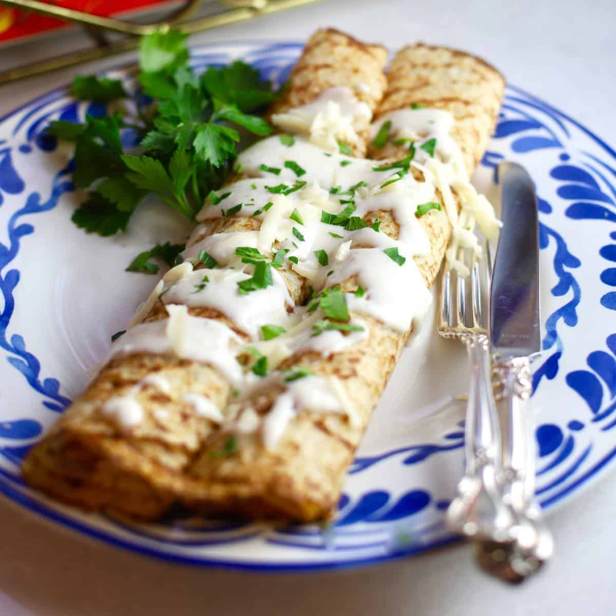 Two crepes on a blue and white plate with chicken and mushroom filling.
