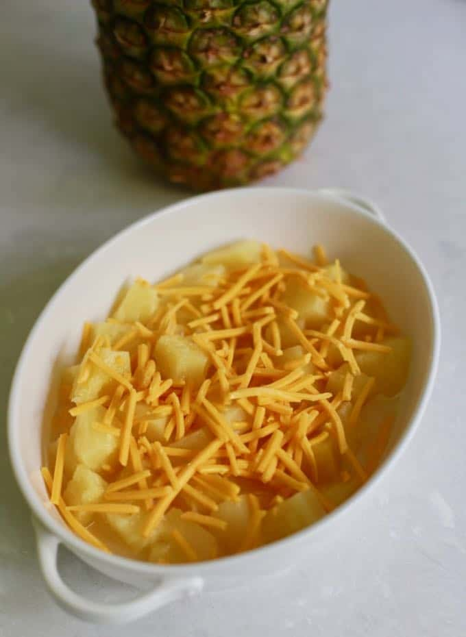 Baked pineapple casserole topped with shredded cheese and ready for the oven.