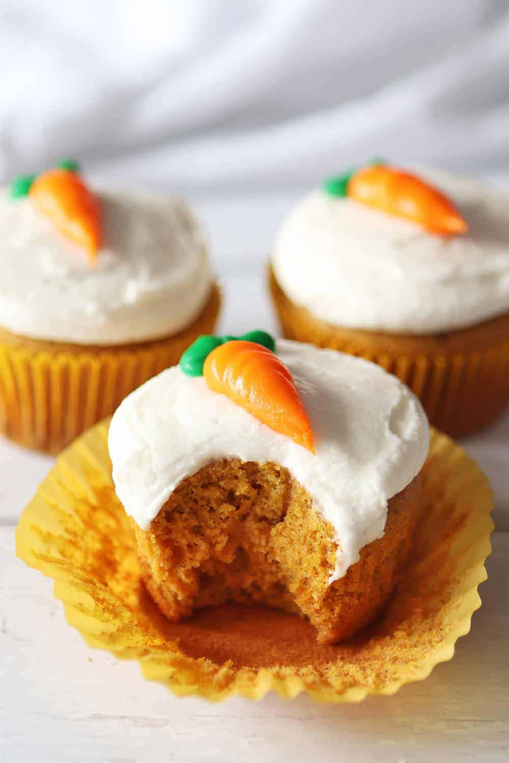Carrot cake cupcakes topped with icing in the shape of a carrot.