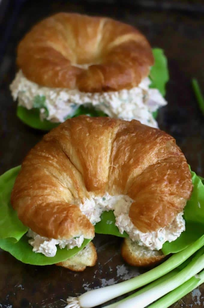 Two croissants with deviled ham filling garnished with scallions.