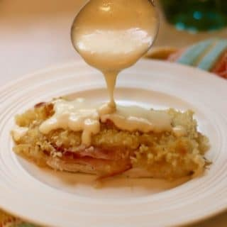 Spooning sauce over Easy Chicken Cordon Bleu Casserole.