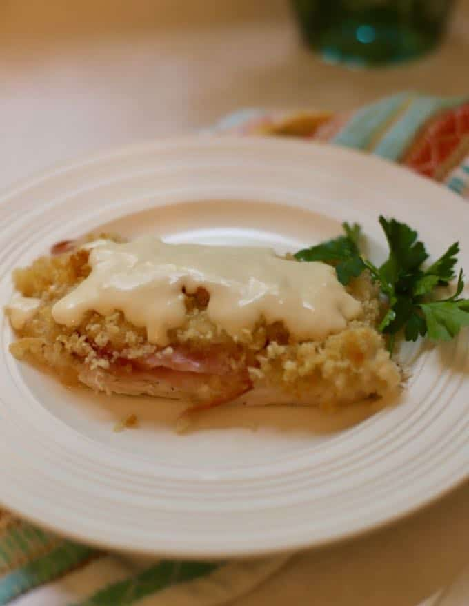 A serving of Oven-baked Chicken Cordon Bleu Casserole on a white plate topped with sauce.