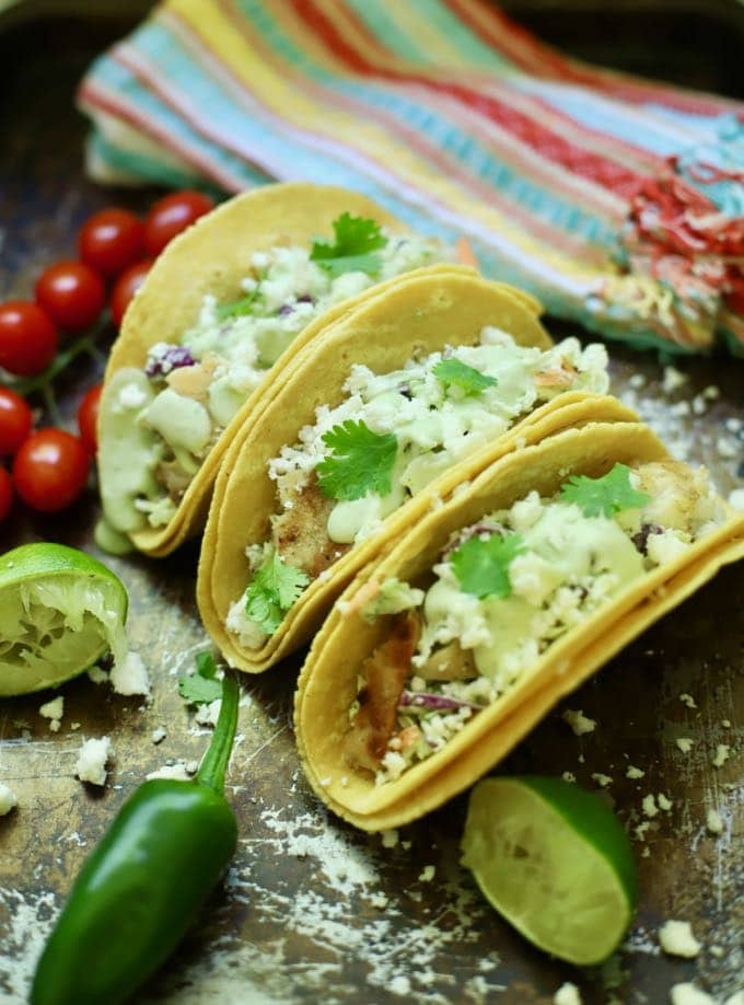 Three grilled fish tacos garnished with cilantro.