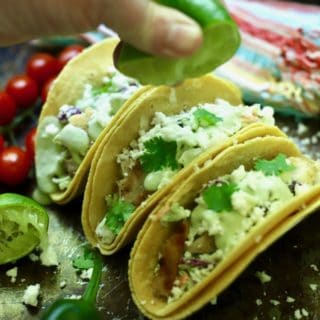 Squeezing lime juice over grilled fish tacos.