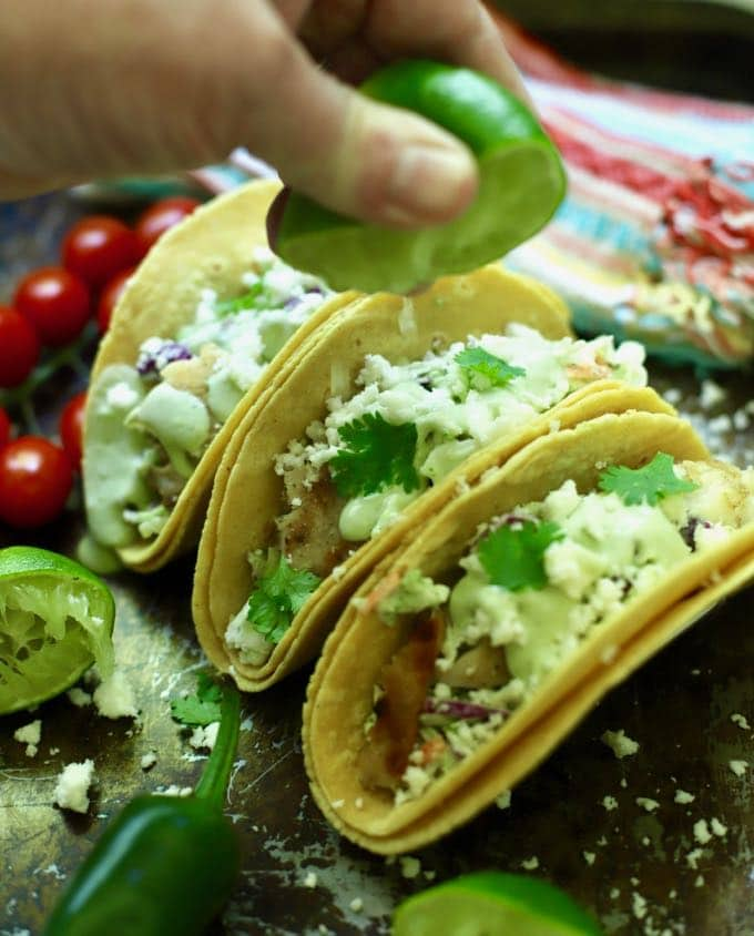 An easy Mexican recipe. Squeezing lime juice over grilled fish tacos.