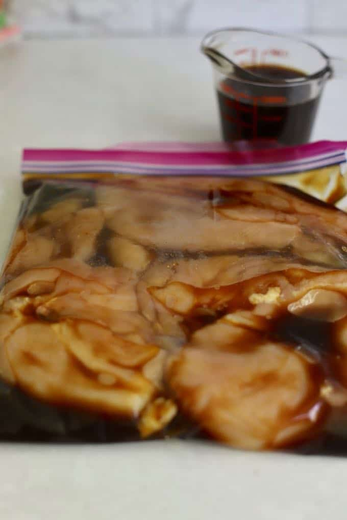 A plastic storage bag full of chicken breasts marinating in teriyaki marinade.