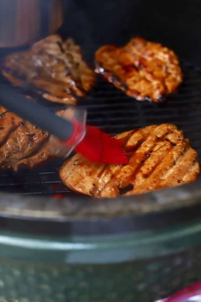 Basting grilled chicken with teriyaki marinade on a grill.