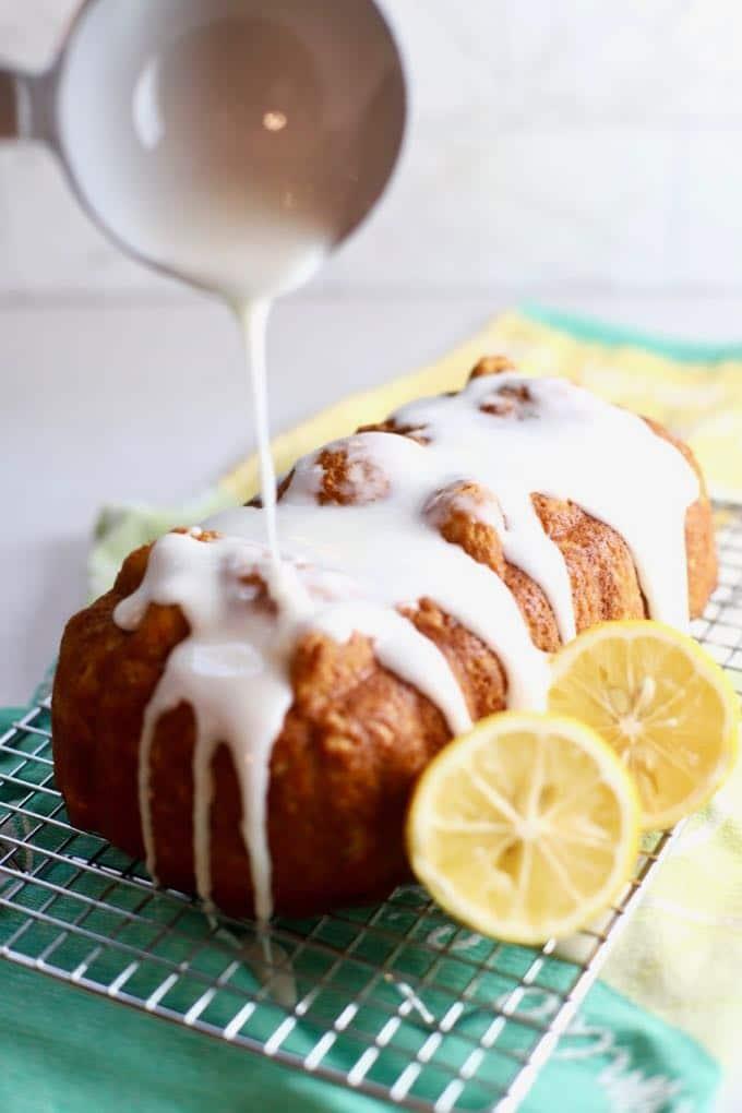 Pouring lemon glaze over a loaf of lemon bread.