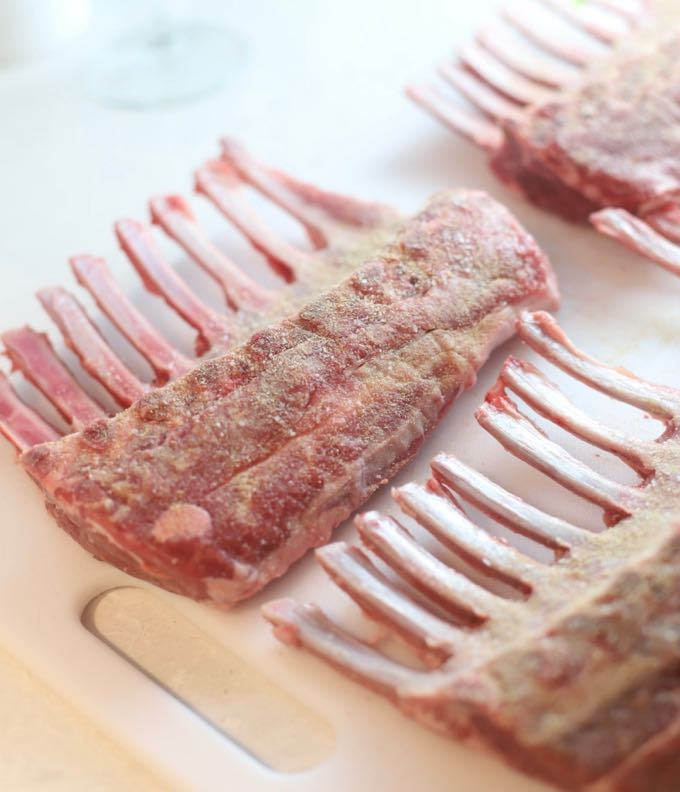 Seasoning the undersides of four racks of lamb with salt and pepper.