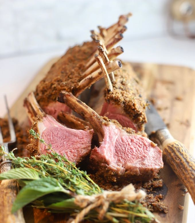Two lamb chops cut from a rack of lamb on a cutting board.