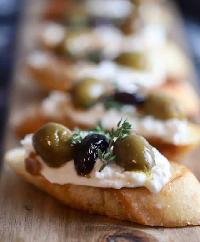 Close up of a bruschetta with burrata and olives on top.