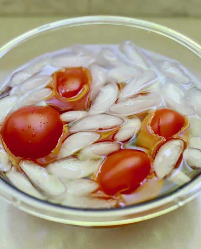 Tomatoes in a clear glass bowl with ice and water.