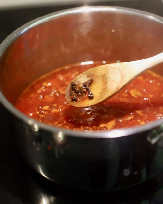 Using a wooden spoon to remove whole cloves from tomatoes and spices cooking in a saucepan.
