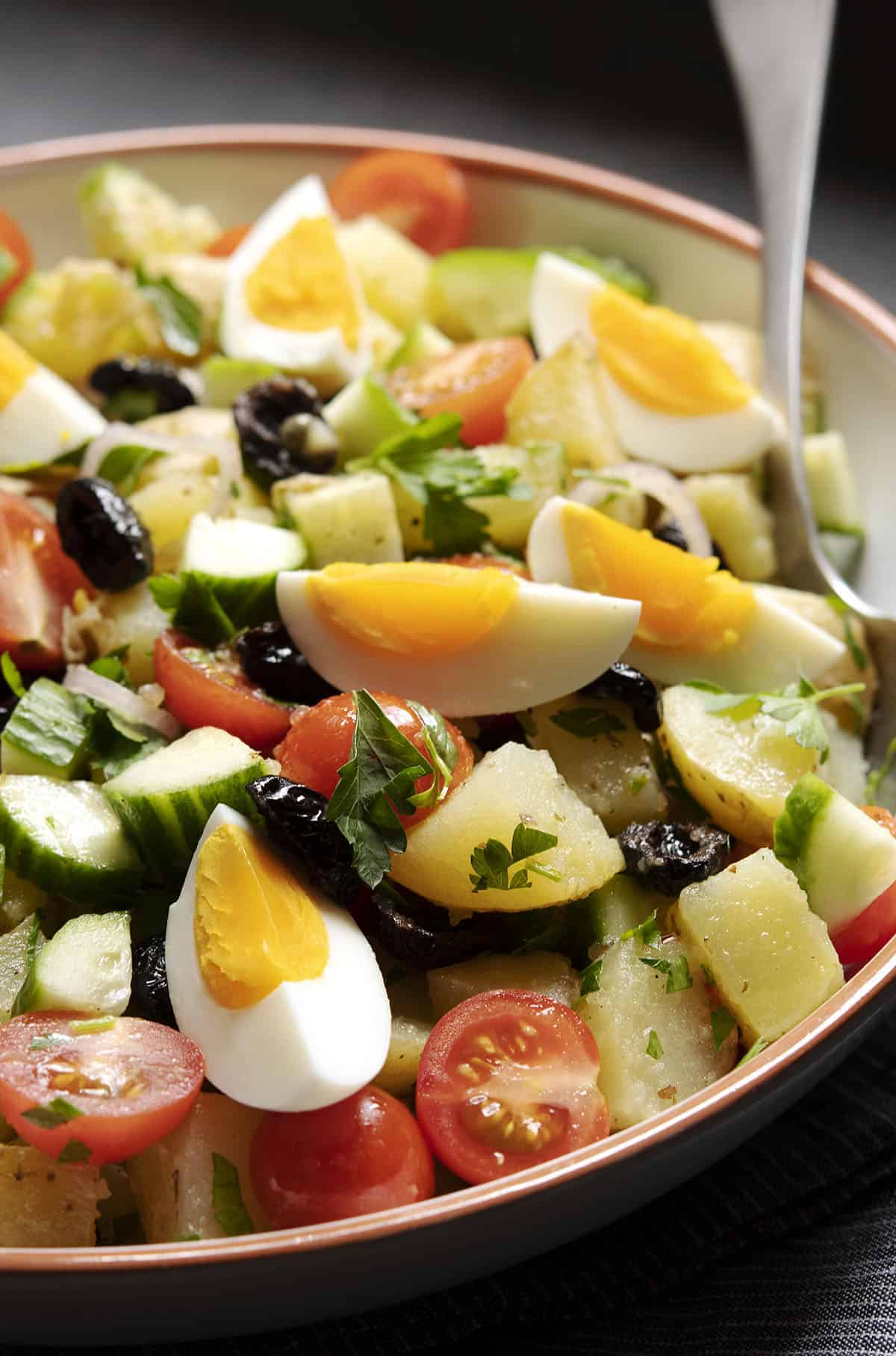 Greek potato salad in a bowl topped with hard-boiled eggs.