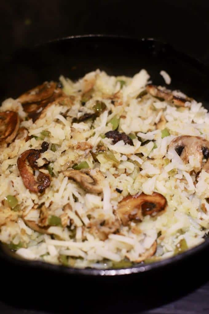 Hash browns and mushrooms cooking in a pan.