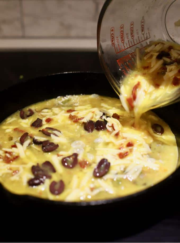 Pouring egg, shredded cheese, olives and sun-dried tomatoes into a pan.