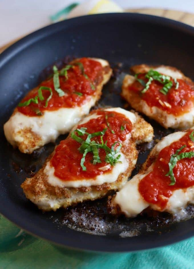 Four chicken breasts in a skillet topped with tomato sauce, mozzarella cheese and chopped basil.