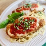 Chicken Parmesan served over spaghetti on a white plate.