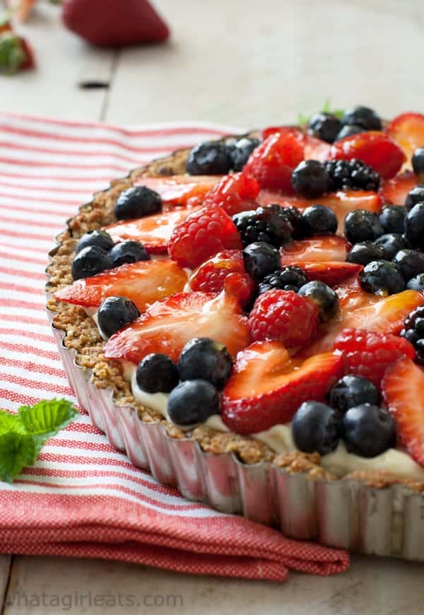 A fruit tart topped with strawberries and blueberries in a tart pan.